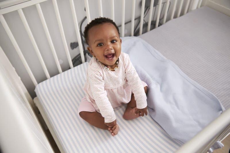 Портрет счастливого ребёнка играя в кроватке питомника стоковые фотографии rf