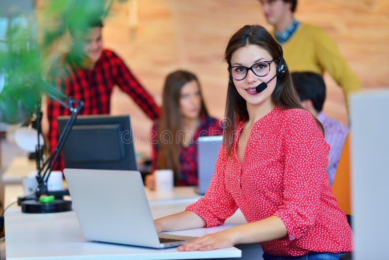 Портрет счастливого усмехаясь женского оператора телефона работы с клиентом на рабочем месте стоковое изображение rf