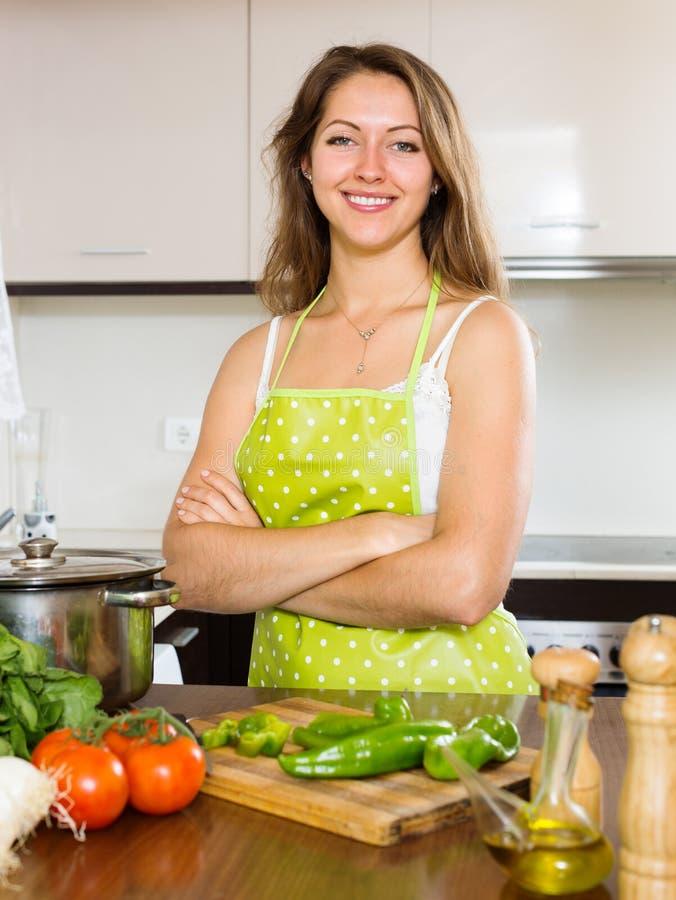 Портрет счастливой девушки варя на кухне стоковая фотография
