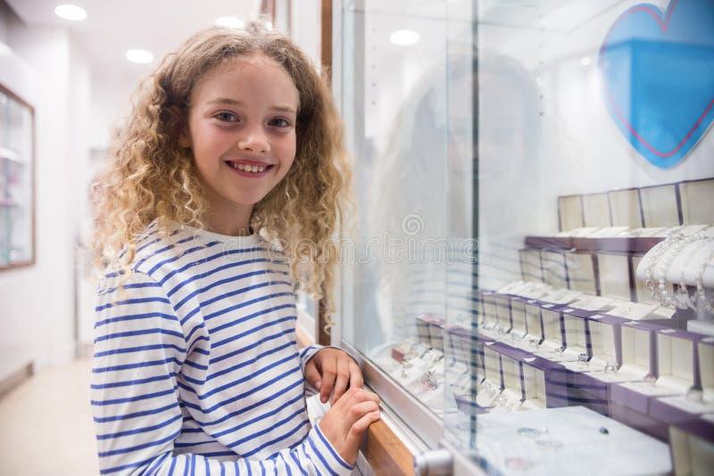 Портрет счастливой девушки стоя близко дисплей ювелирных изделий стоковая фотография rf