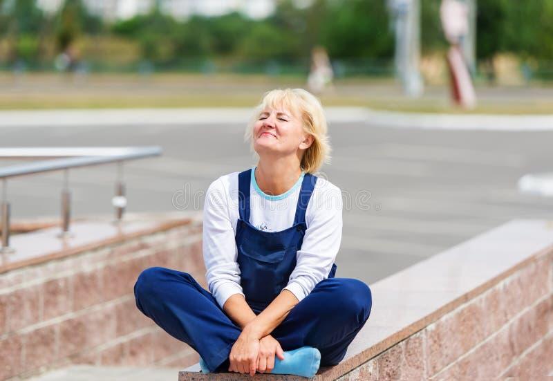 Портрет счастливой женщины в форме сидя в представлении лотоса стоковая фотография rf