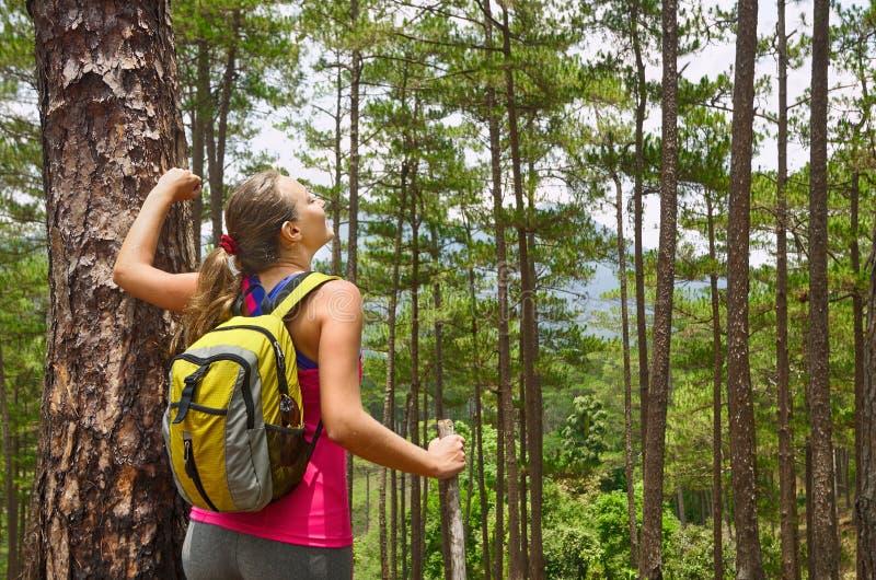 Портрет счастливой женщины путешественника в лесе наслаждаясь солнечным днем стоковое фото