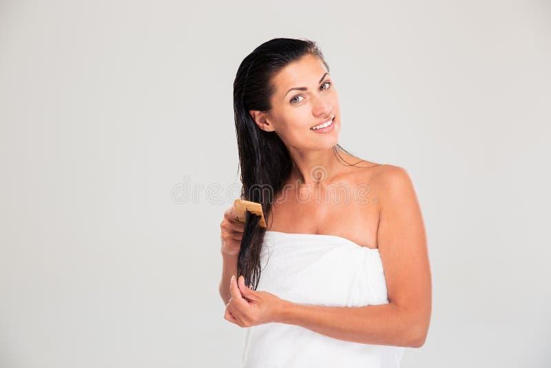 Портрет счастливой женщины расчесывая ее волосы стоковые изображения