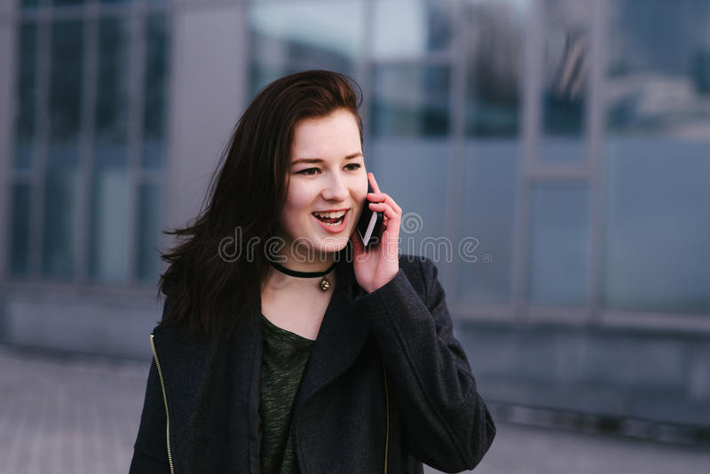 Портрет счастливой и стильно одетой женщины говорит на телефоне на городе темную предпосылку стоковые фото