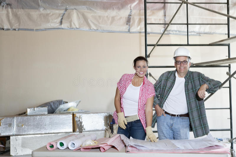 Портрет счастливой команды архитекторов с зданием планирует на строительной площадке стоковое изображение
