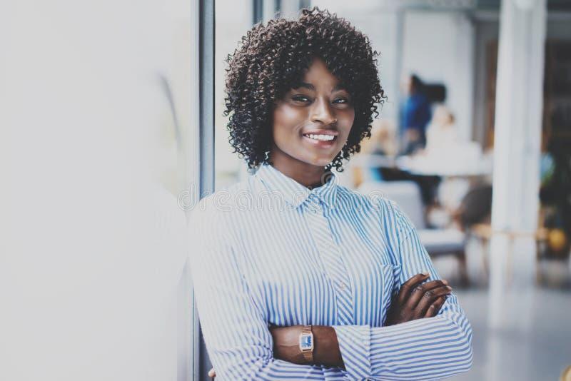 Портрет счастливой красивой африканской женщины стоя с сложенными оружиями и коллегами на предпосылке в современной просторной кв стоковое фото rf