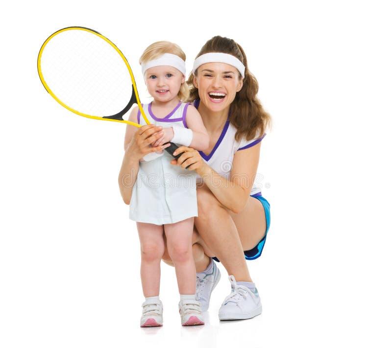 Портрет счастливой матери и младенца держа ракетку тенниса стоковая фотография rf