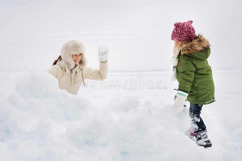 Портрет счастливой матери и ребенок играя снежный ком воюют стоковые изображения rf