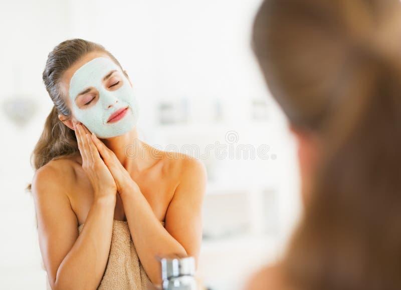 Портрет счастливой молодой женщины с косметической маской на стороне стоковое изображение rf