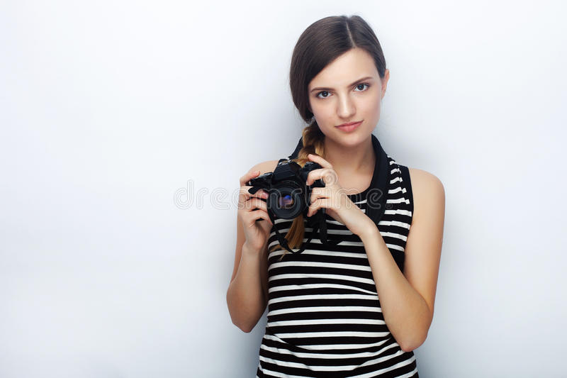 Портрет счастливой молодой красивой женщины в striped рубашке представляя с черной камерой фото против предпосылки студии стоковые фотографии rf