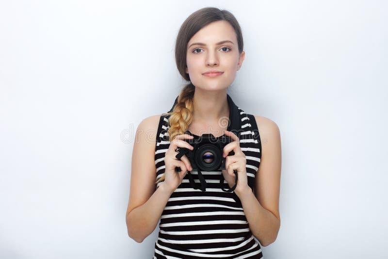 Портрет счастливой молодой красивой женщины в striped рубашке представляя с черной камерой фото против предпосылки студии стоковая фотография