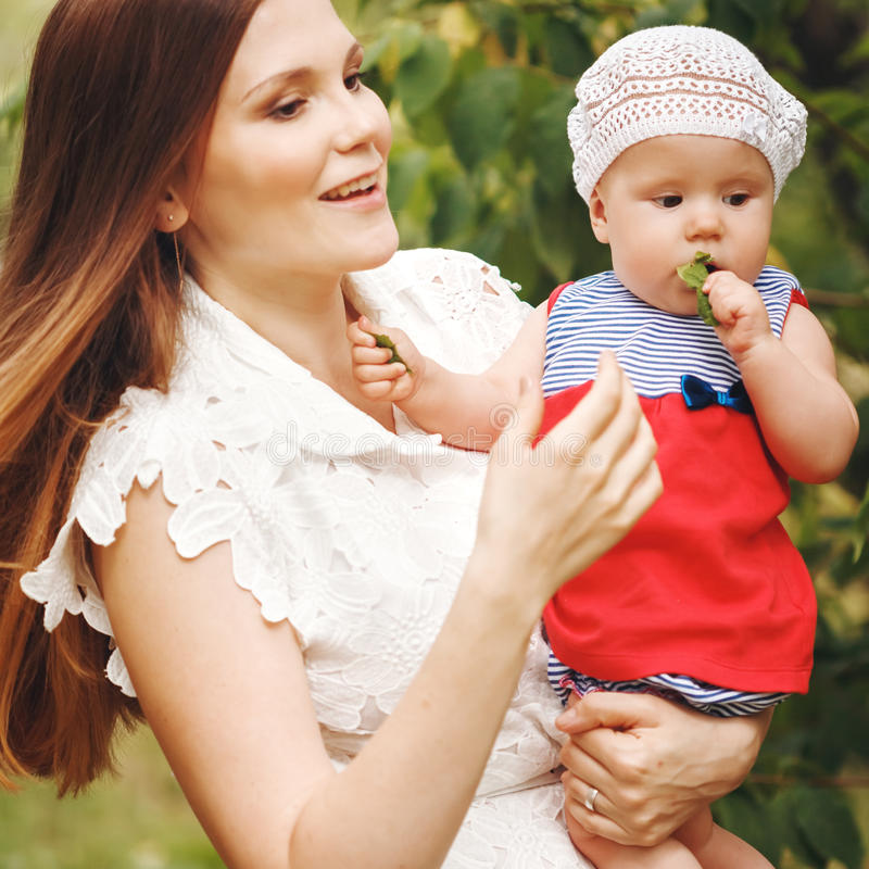 Портрет счастливой молодой матери держа ее младенца стоковое фото