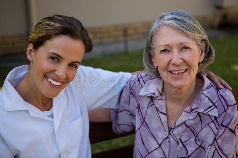 Портрет счастливой старших женщины и доктора сидя на стенде стоковая фотография