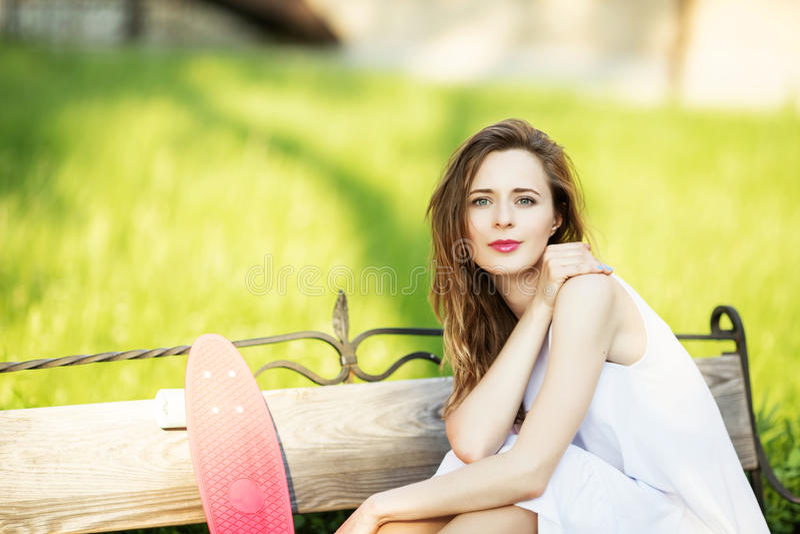 Портрет счастливой усмехаясь молодой женщины с розовым скейтбордом стоковая фотография rf