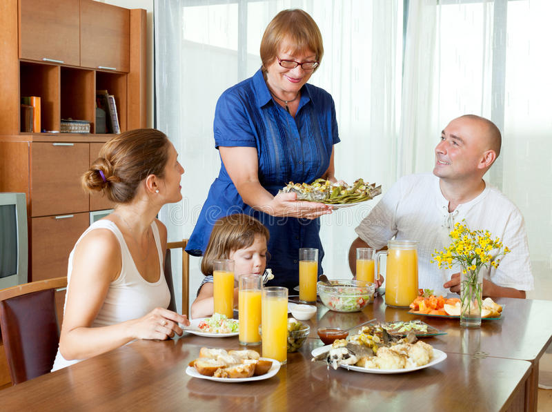 Портрет счастливой multigeneration семьи есть рыб с соком стоковое фото rf