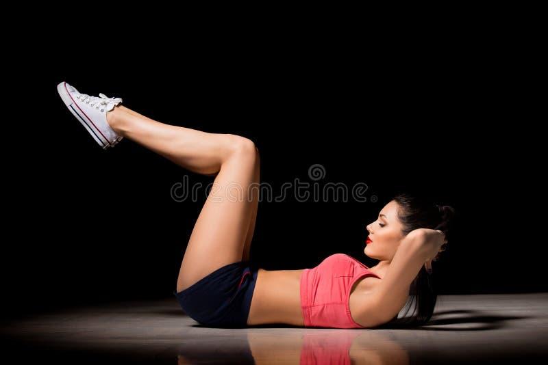 Портрет счастливой sporty женщины делая тренировку abs Радостный женский модельный тренировать внутри помещения Здоровый активный стоковая фотография rf