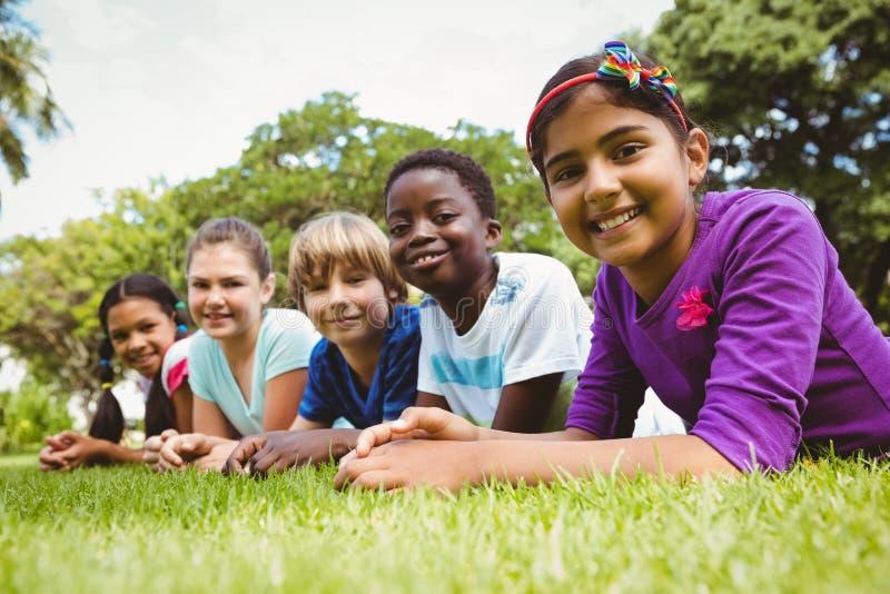 Портрет счастливых детей лежа на траве стоковые изображения