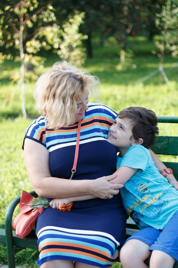 Портрет счастливых матери и сына усмехаясь outdoors стоковые изображения