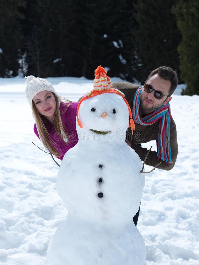 Портрет счастливых молодых пар с снеговиком стоковые изображения rf