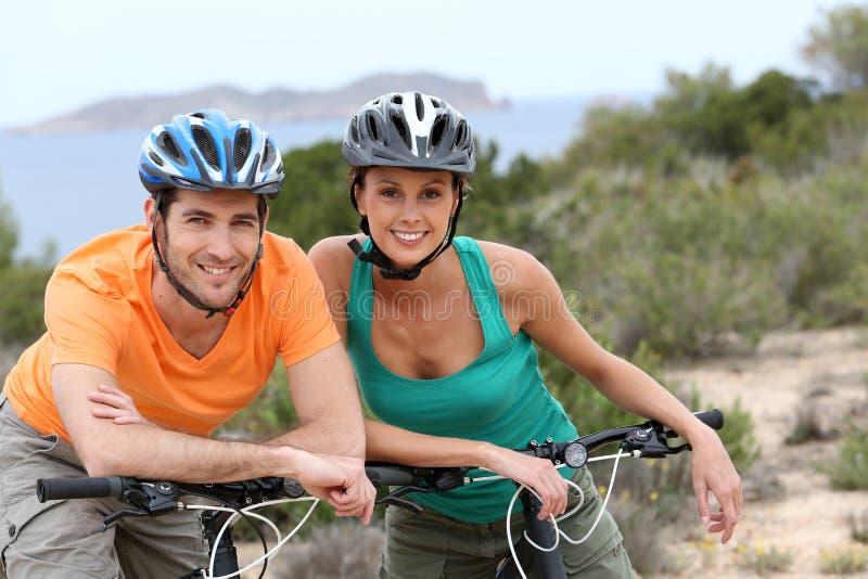 Портрет счастливых пар велосипедистов на отключении стоковое изображение