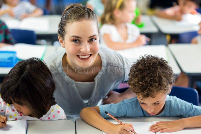 Портрет счастливых школьников порции учительницы стоковые изображения rf
