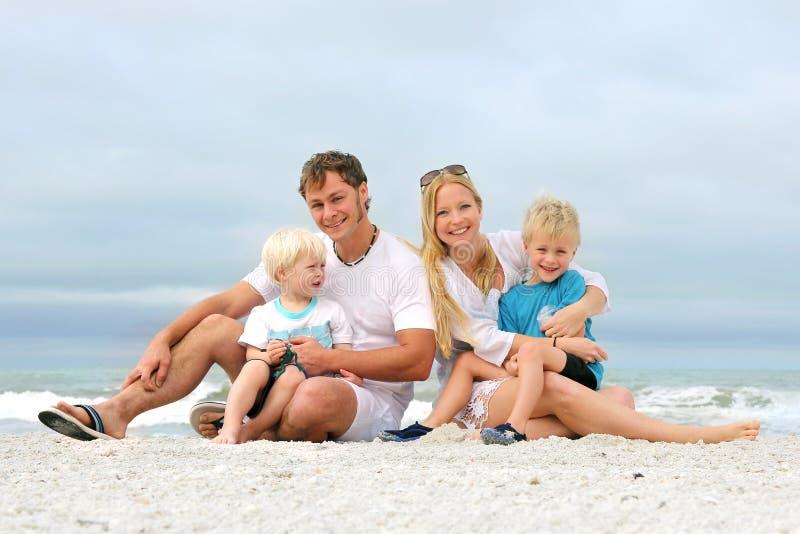 Портрет счастливых людей семьи из четырех человек ослабляя на пляже стоковая фотография rf