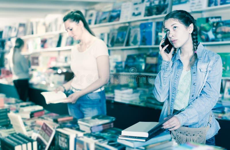 Портрет славных учебников и говорить рудоразборки девушки на телефоне стоковая фотография