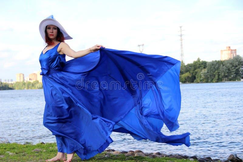 Портрет с полным ростом на берегах реки, в ветрено теплый летний день женщина в красивом длинно-голубом платье стоковое изображение rf