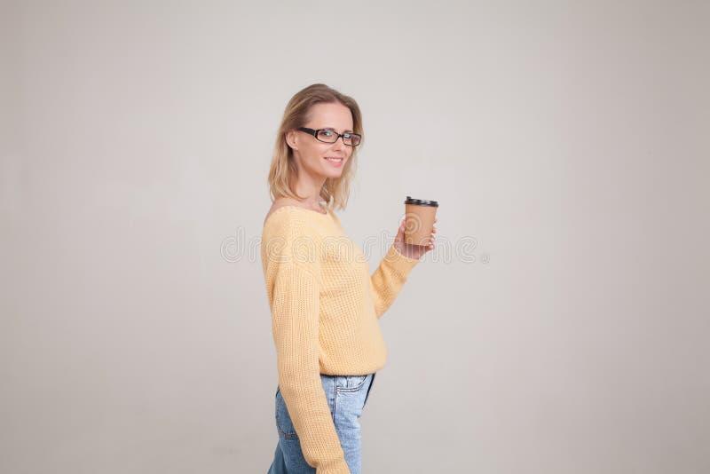 Портрет талии-вверх белокурой женщины держа крышку кофе в ее руках и усмехаясь, смотря камеру нося желтый свитер и стоковое фото