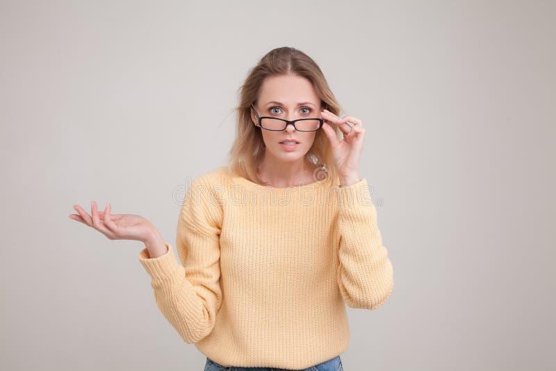 Портрет талии-вверх молодой белокурой женщины с удивленной эмоцией на ее стороне смотрящ камеру, замечает что-то непредвиденное, стоковые изображения rf