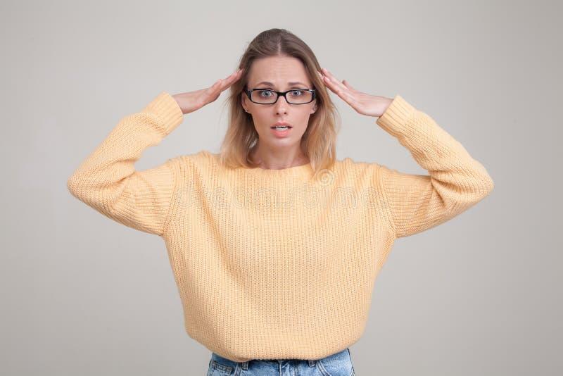 Портрет талии-вверх молодой белокурой женщины с удивленной эмоцией на ее стороне смотрящ камеру, замечает что-то непредвиденное, стоковые фото