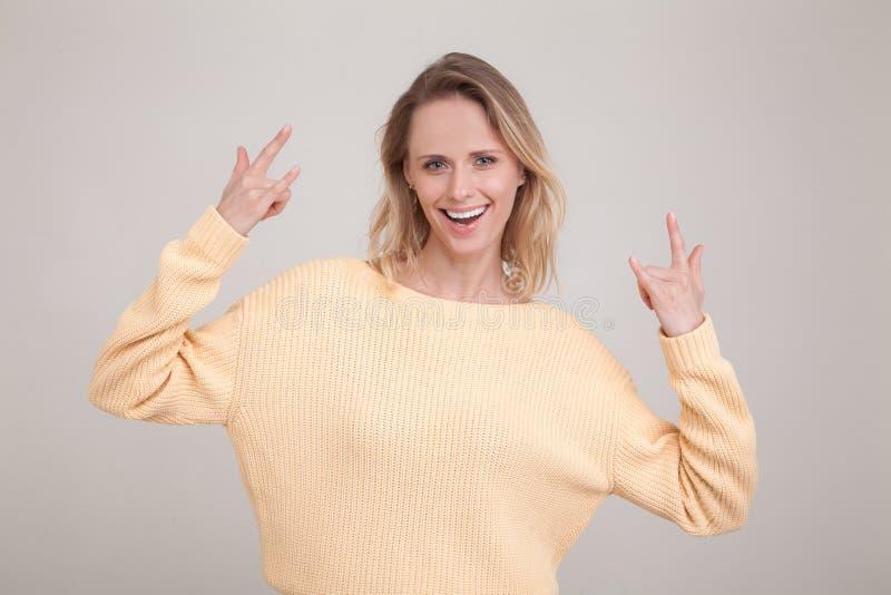 Портрет талии-вверх счастливой белокурой женщины с удовлетворенной беспечальной ориентацией, показывающ жесты крена n утеса, усме стоковое изображение rf