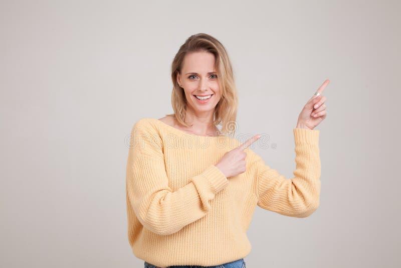 Портрет талии-вверх счастливой усмехаясь белокурой женщины указывая пальцы прочь, показывающ что-то интересное и выход, смотря стоковые фото