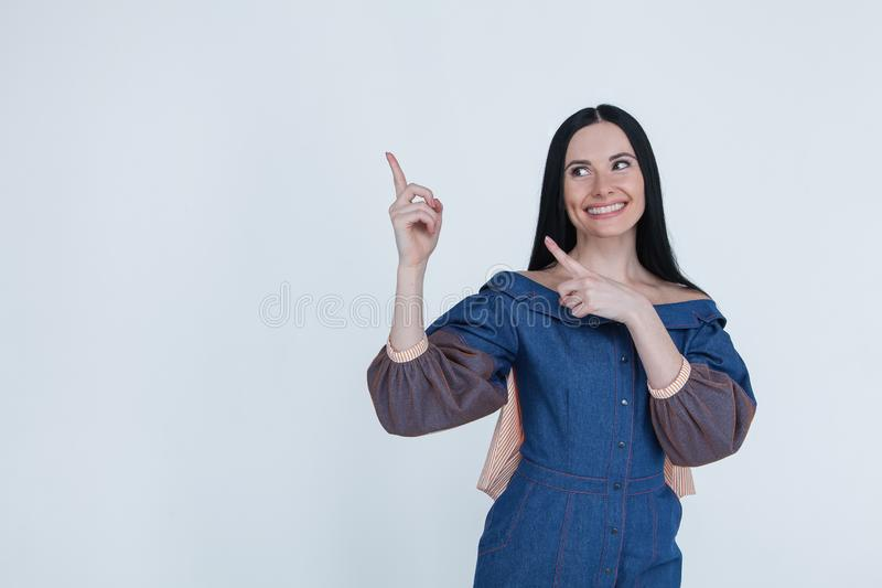 Портрет талии-вверх счастливой усмехаясь женщины брюнета указывая пальцы на левый угол, космос для вашего текста или логотип Одет стоковые изображения rf