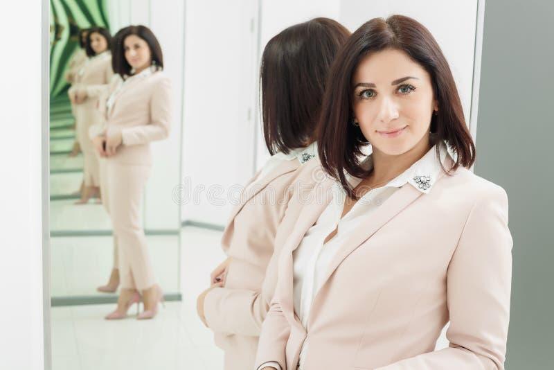 Портрет темн-с волосами привлекательной женщины которая одета в бежевом костюме стоять в переднем зеркале стоковое изображение rf