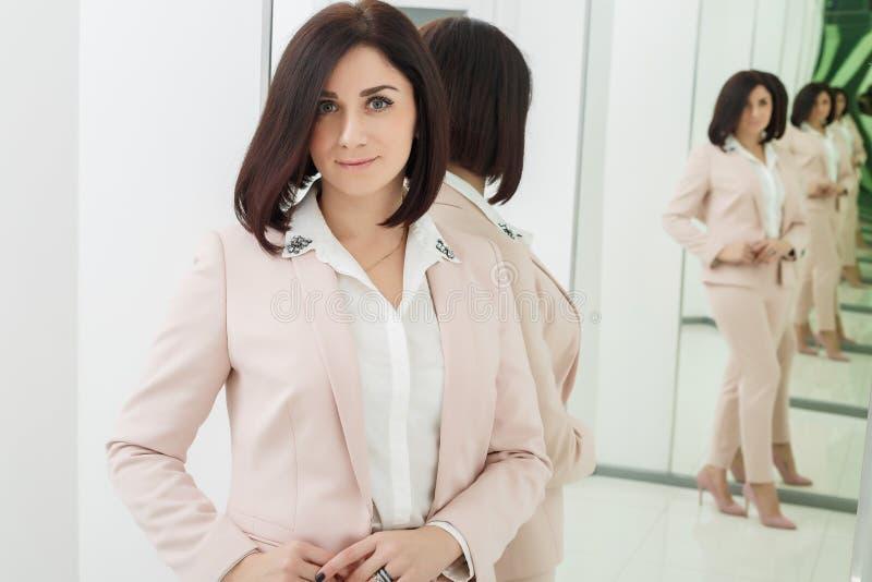 Портрет темн-с волосами привлекательной женщины которая одета в бежевом костюме стоять в переднем зеркале стоковые фото