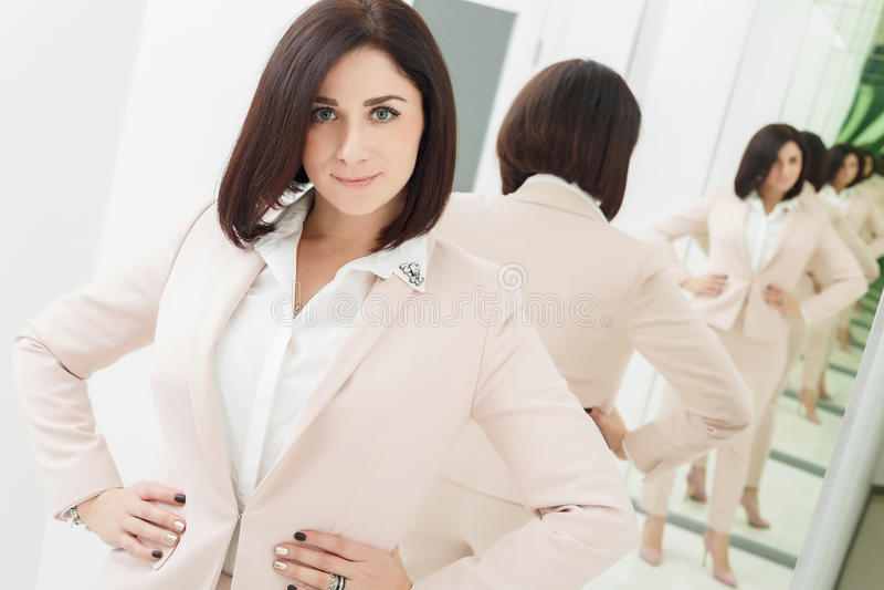 Портрет темн-с волосами привлекательной женщины которая одета в бежевом костюме стоять в переднем зеркале стоковое изображение