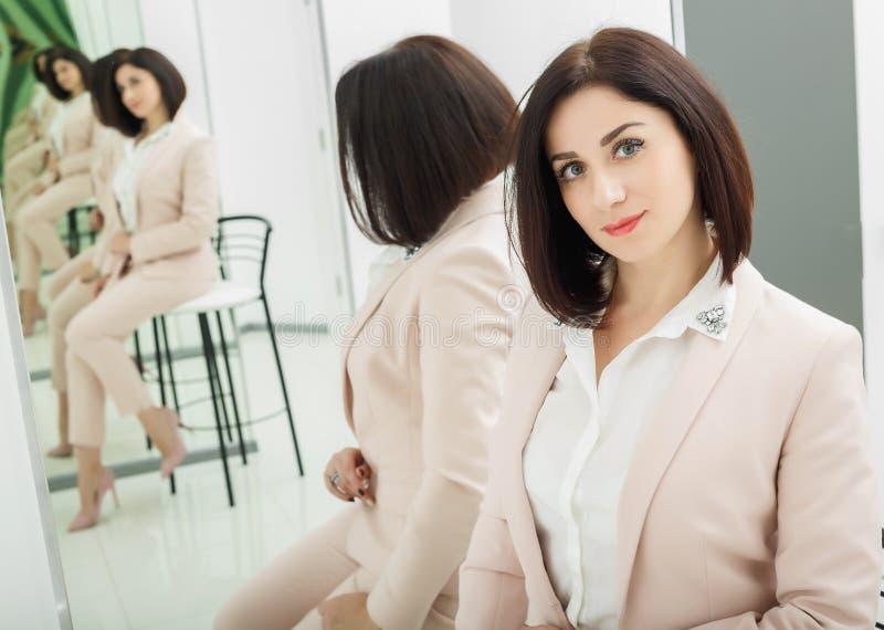 Портрет темн-с волосами привлекательной женщины которая одета в бежевом костюме стоять в переднем зеркале стоковая фотография rf
