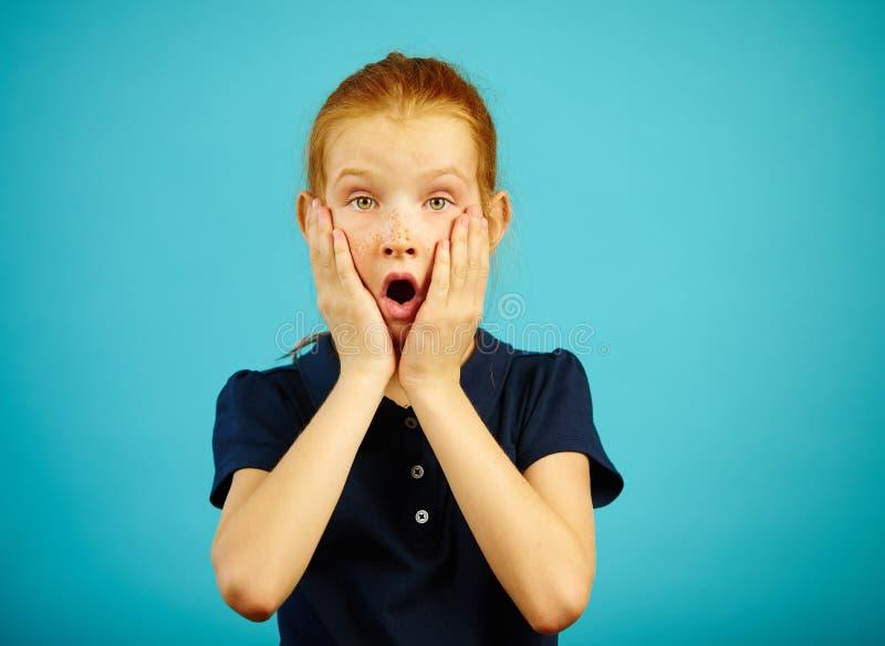 Портрет трепетной девушки с произнесенной эмоцией страха, кладет его руки на щеку, выражает stunned и паника, имеет a стоковые изображения
