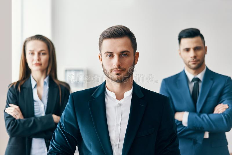 Портрет уверенного красивого бизнесмена в офисе с его командой на предпосылке стоковая фотография rf