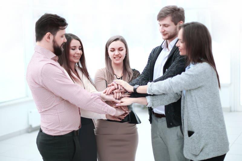 Портрет уверенной команды дела штабелируя руки стоковое изображение