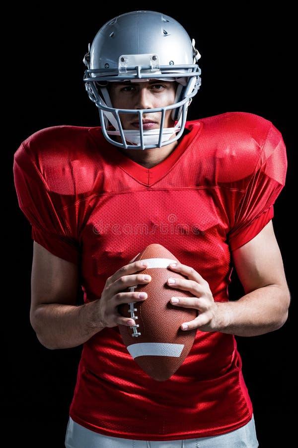 Портрет уверенно американского футболиста держа шарик стоковая фотография