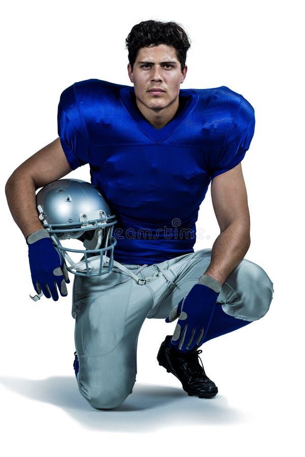 Портрет уверенно американского футболиста держа шлем стоковое изображение