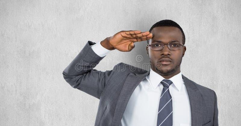 Портрет уверенно бизнесмена салютуя против серой предпосылки стоковые изображения rf