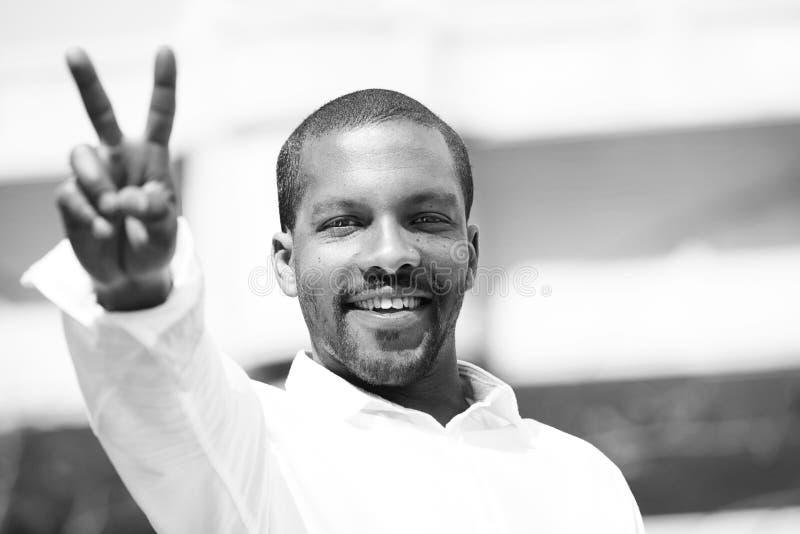 Портрет уверенно молодого Афро-американского битника человека в белой рубашке показывая символ v пальцев Голубое небо с облаками  стоковые фотографии rf