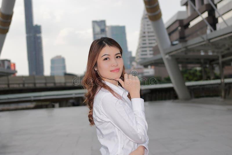 Портрет уверенно молодой азиатской женщины при белая рубашка смотря на камере на городской предпосылке публики здания стоковые фото