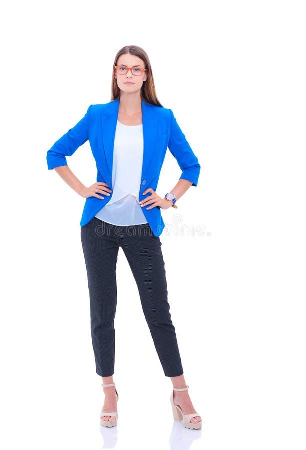 Портрет уверенно молодой женщины стоя на белой предпосылке стоковое изображение rf