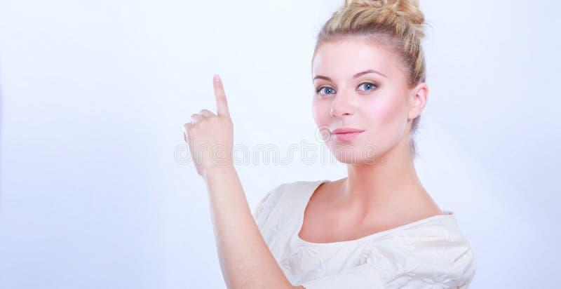 Портрет уверенно положения и указывать молодой женщины изолированных на белой предпосылке стоковое изображение rf