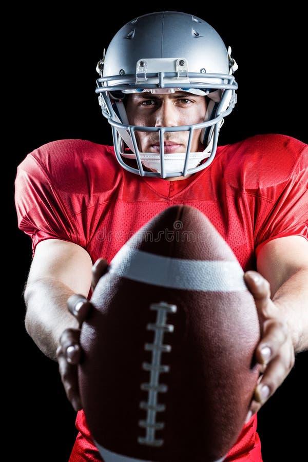 Портрет уверенно спортсмена показывая американский футбол стоковое изображение