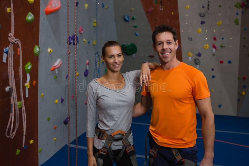 Портрет уверенно спортсменов готовя взбираясь стену в спортзале стоковые изображения rf